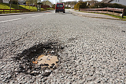 car and pothole