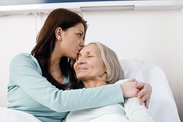 Woman kissing mother at hospital