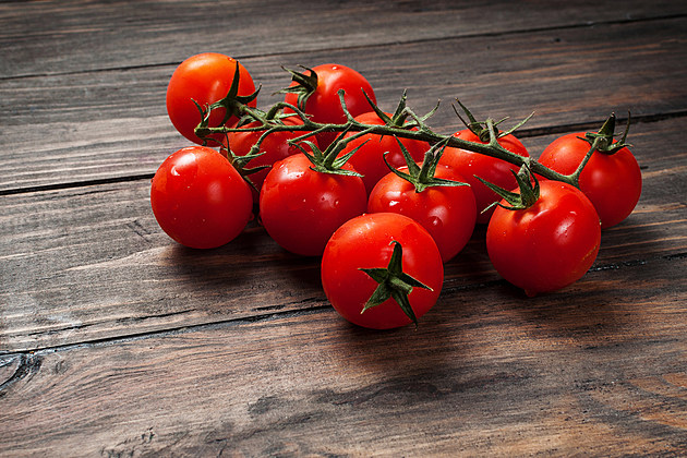 Fresh cherry tomatoes on wood background